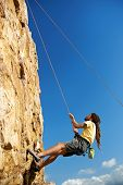 picture of harness  - A man in a harness holding on to a rope while climbing up a steep mountain  - JPG