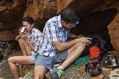 image of cave woman  - A hiking couple taking a break by a cave with their hiking utensils around them - JPG