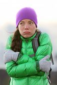 foto of shivering  - Freezing woman feeling cold outdoors trying to keep warm shaking and shivering wearing hat and gloves outside hiking on hike - JPG