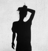 stock photo of forehead  - shadow of tired woman wiping forehead around on wall background - JPG