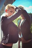 stock photo of blazer  - young blue eyes woman with short blonde hair in elegant  black blazer reflection in glass - JPG