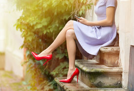 stock photo of stiletto  - Fashionable woman in red high heels sitting outside on stairs and using mobile phone - JPG
