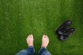 stock photo of legs feet  - Mens feet resting on green soft grass - JPG