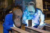 foto of welding  - Two steel construction workers welding metal pieces - JPG