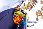 image of ropeway  - Boy and young mom sit on ski lift on mountain winter resort wearing colorful clothes and skimasks - JPG