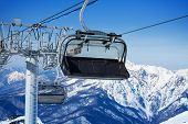 picture of ropeway  - Close view of skilift chair on ropeway over mountains on background on winter ski resort - JPG