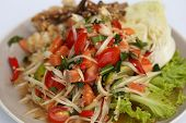 image of green papaya salad  - papaya spicy salad with salmon on white table in restaurant - JPG
