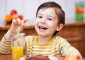 pic of orange-juice  - Little boy is drinking orange juice using straw - JPG