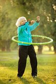 picture of 70-year-old  - 70 years old Senior Woman doing Exercises with the Plastic Hoop at the Green Meadow in the Bright Autumn Evening - JPG