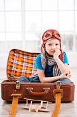 image of little boys only  - Bored little boy in pilot headwear and eyeglasses holding hand on chin and looking at camera while sitting inside of briefcase at home - JPG