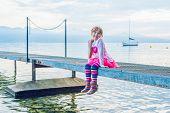 foto of pier a lake  - Portrait of a cute little girl sitting on a pier on a quiet lake side - JPG