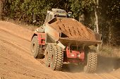 image of dump_truck  - A large articulated dump truck moves top soil pile for later use on a new commercial construction development project - JPG
