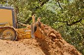 image of bulldozers  - Small bulldozer moving dirt from a hillside in preperation for a new commerical construction development - JPG