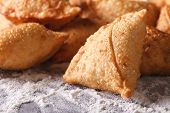 stock photo of samosa  - A pile of baking samosas macro on the table with flour - JPG