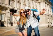 stock photo of selfie  - young beautiful friends tourist couple visiting Spain in holidays exchange students and taking selfie stick picture together in town happy on sunny day in travel and vacation concept - JPG