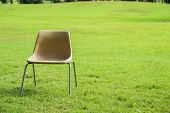 foto of lawn chair  - old plastic chair with stainless support on green lawn - JPG