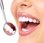 stock photo of dentist  - Healthy woman teeth and a dentist mouth mirror - JPG