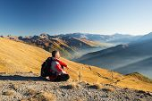 picture of italian alps  - Male hiker relaxing at sunset at the mountain summit and looking at majestic panorama of the italian Alps with dirt road crossing colorful meadows in autumn season and misty valley below.