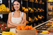 picture of apron  - Beautiful young woman in apron keeping arms crossed and smiling while standing in grocery store with variety of fruits in the background - JPG
