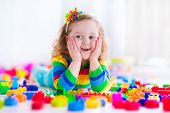image of kindergarten  - Cute funny preschooler little girl in a colorful shirt playing with construction toy blocks building a tower in a sunny kindergarten room - JPG
