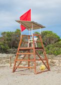 picture of lifeguard  - Empty lifeguard tower with red flag on the beach - JPG
