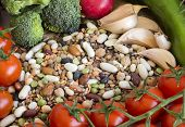 stock photo of legume  - Mixed legumes and vegetables on a wooden table - JPG
