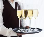 image of waiter  - Professional male waiter in uniform serving champagne - JPG