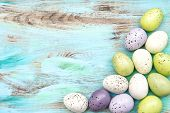 stock photo of nostalgic  - Pastel colored easter eggs on wooden background - JPG