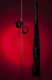 picture of bondage  - bdsm toys hanging on a red background - JPG