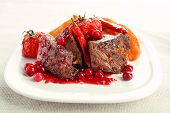picture of deer meat  - Tasty roasted meat with cranberry sauce and roasted vegetables on plate - JPG