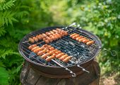 stock photo of grilled sausage  - Tasty sausages on a round grill outdoors - JPG