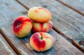 image of saturn  - Fresh Saturn peaches on old wooden background - JPG