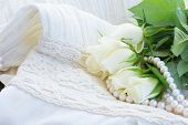 stock photo of mother-of-pearl  - white fresh  rose flowers with  pearls on white lace background - JPG