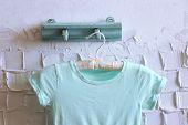 stock photo of habilis  - Child dress on hanger on white wall background - JPG