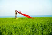 picture of rune  - Young lady runing with tissue in green field - JPG
