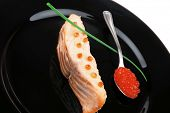 Постер, плакат: savory sea fish portion : roasted salmon fillet with green onion and red caviar in spoon on black di