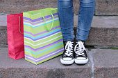 picture of street-walker  - Female feet in gumshoes near shopping bag on  stone stairs - JPG
