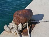 picture of bollard  - Rusty mooring bollard with ship ropes at the quay of the city Biograd at the mainland of Croatia - JPG