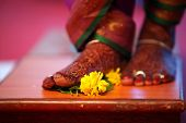 stock photo of mehendi  - The feet of a traditional Indian bride decorated with Mehendi or Henna standing near a flower on a wooden plank as a part of a hindu wedding ritual - JPG