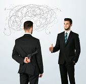 pic of backstabbers  - Ruthless businessman hiding a weapon and weaving plan around his head - JPG