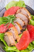 stock photo of roast duck  - Roast duck breast with lettuce and grapefruit on a plate - JPG