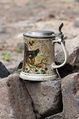 picture of pitcher  - Old painted porcelain pitcher standing on basalt rocks - JPG
