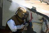 pic of sandblasting  - Worker is removing paint by air pressure sand blasting - JPG