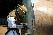 image of sandblasting  - Worker is removing paint by air pressure sand blasting - JPG