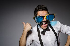 image of moustache  - Young man with false moustache and large sunglasses isolated on gray - JPG
