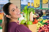 stock photo of grocery-shopping  - Young woman holding a grocery bag full of fresh and healthy food inside a supermarket - JPG