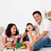 stock photo of family fun  - Happy family with parents and daughter playing with colorful blocks inside at home - JPG