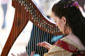 picture of musical instrument string  - A woman playing a harp - JPG