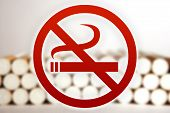 picture of cigarette-smoking  - Red no smoking sign in front of a blurry picture of cigarettes - JPG