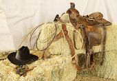 stock photo of brahma-bull  - Saddle hat rope and gloves resting on hay bales - JPG